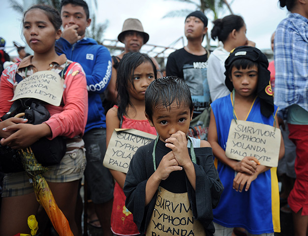 Survivors of the super Typhoon Haiyan, wait for a C-130 military plane at T